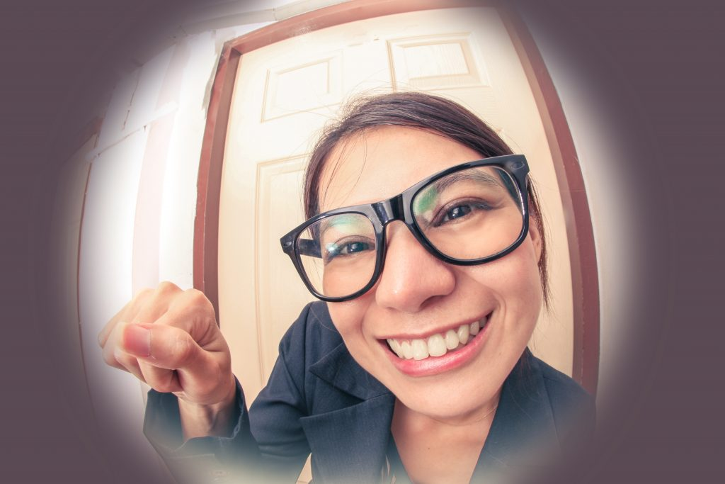 woman knocking at door seen through a peephole and smiling