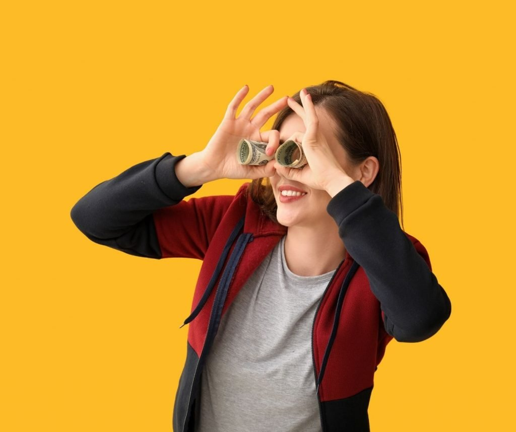 Woman with rolled up dollar notes as binoculars - fun money
