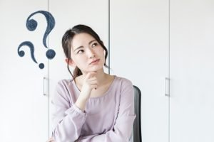 Woman thinking with question marks next to her head